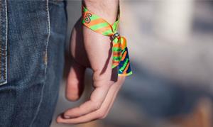 Personne portant au poignet un bracelet en tissu personnalisé.