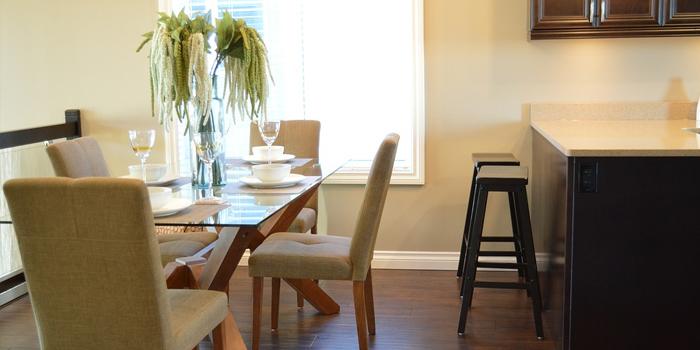 Chaises de couleur claire placées autour de la table de salle à manger.